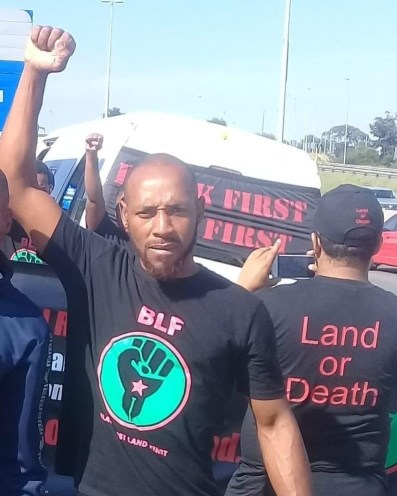 "BLF member with t-shirt that reads, ""Land or Death"""