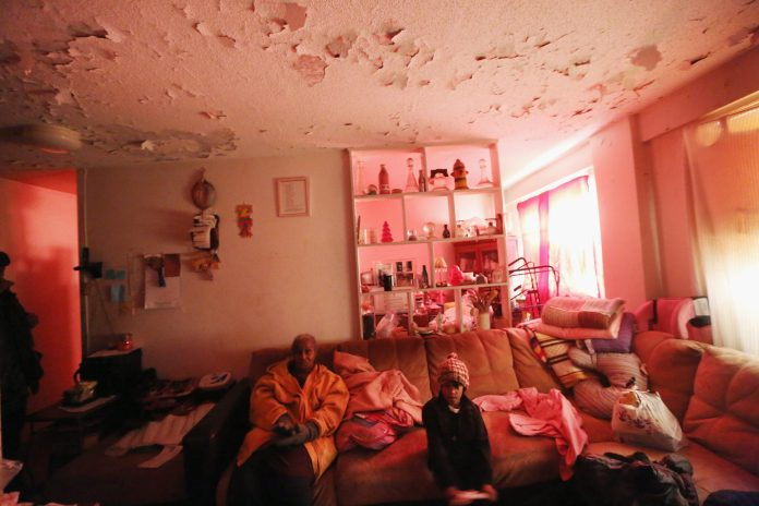 Picture of a grandmother and very young granddaughter in a run down living room