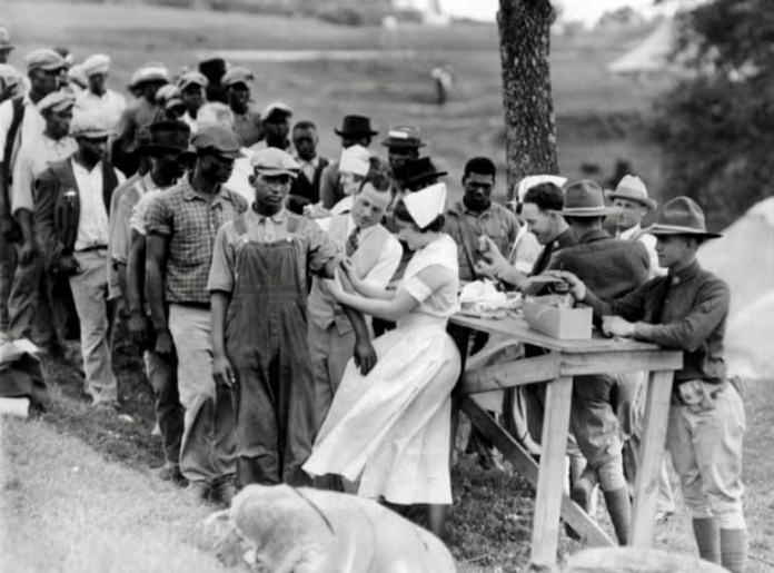 African men in the Tuskegee experiment stand in line, waiting on a white nurse.