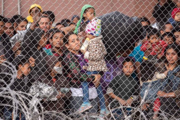 Migrants are gathered inside the fence of a makeshift detention center in El Paso, Texas on Wed. March 27, 2019. Sergio Flores—The Washington Post/Getty Images