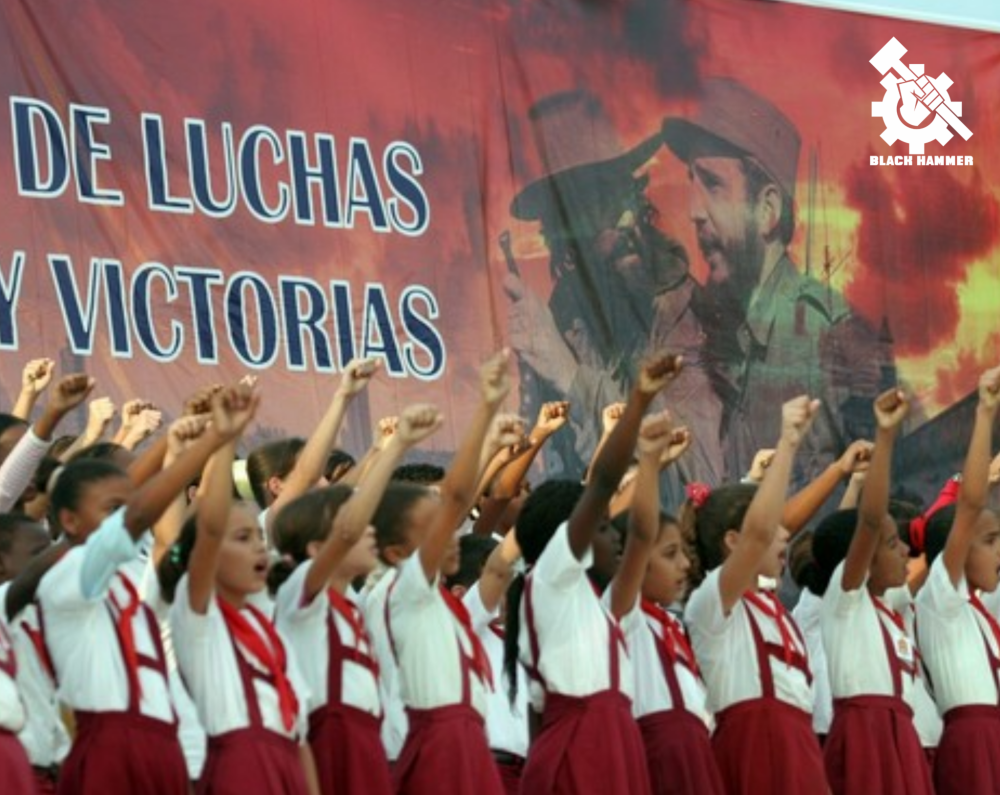 Cuban school children raising fist in front of banner of Fidel Castro