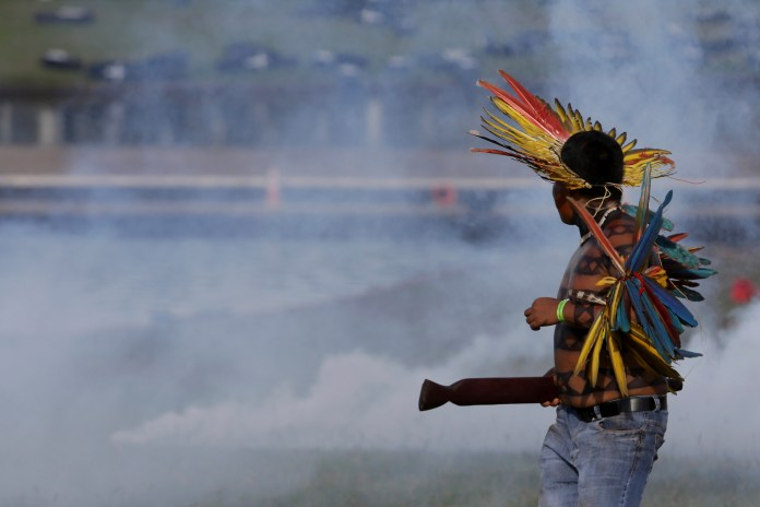An Indigenous man looks through tear gas fired by police outside the National Congress during a protest for the demarcation of indigenous lands in Brasilia, Brazil, Tuesday, April 25, 2017 (AP Photo/Eraldo Peres)
