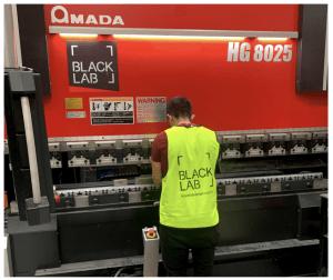 man bending metal on amada machine