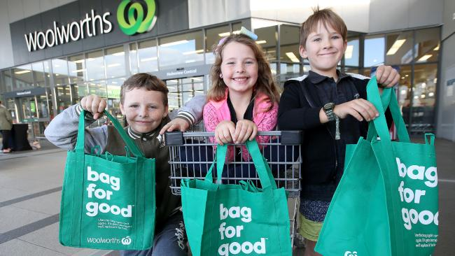 three kids holding woolworths sustainable bags