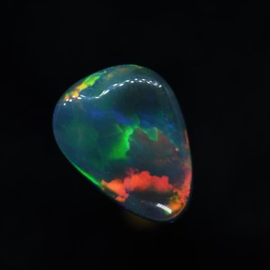 This is a very nice natural solid black opal with a fantastic broad flash pattern and directional reds, green, orange mixed with blue undertones.