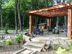 pergola built on stone patio with fire pit