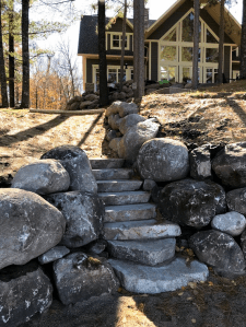Lakefront landscaping with boulder walls and steps