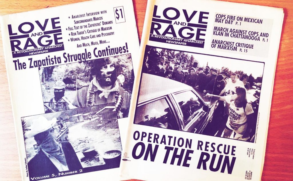 Photo of two editions of Love and Rage newspaper. The cover for one discusses the Zapatista movement, the other abortion clinic defense.