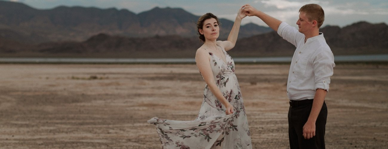 Groom spins bride and flowy dress billows