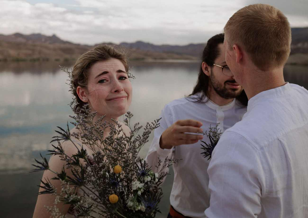 Bride looks at camera crying at Nelson's Landing on the cliff