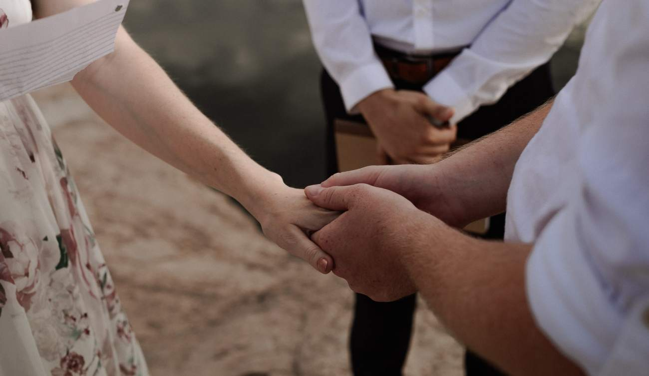 Groom holds bride's hand during ceremony