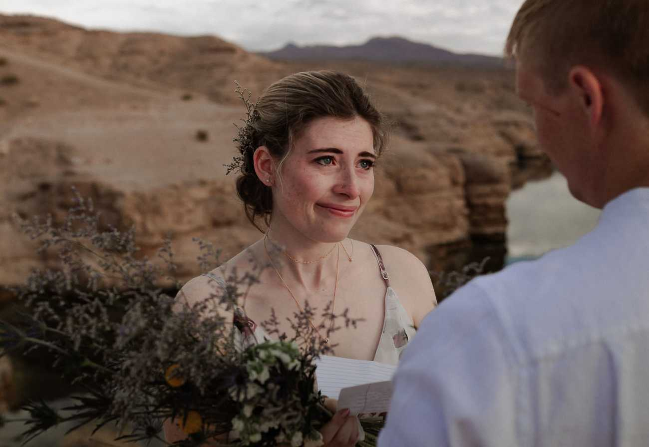 Bride cries while groom reads vows