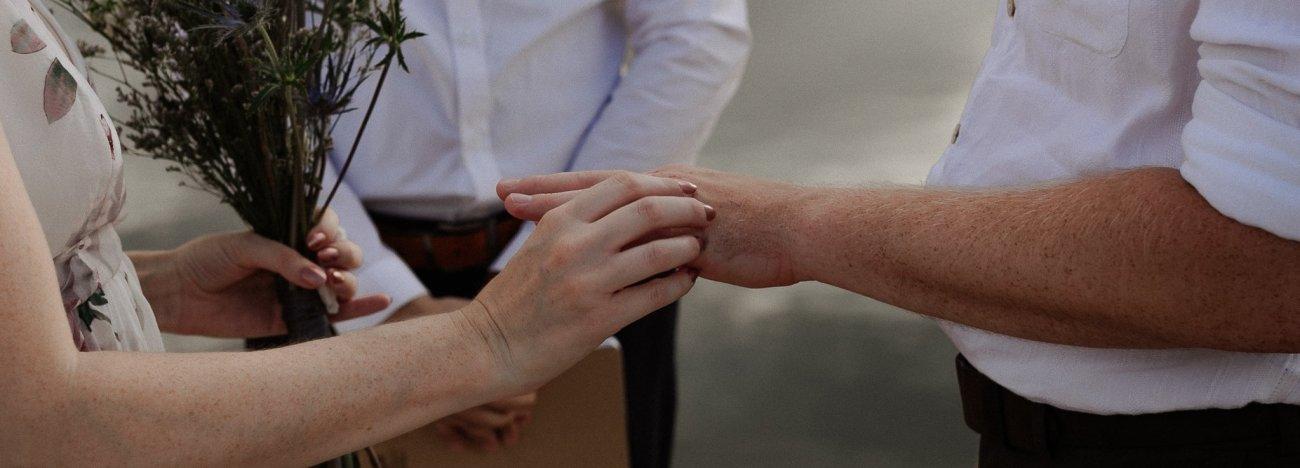 Bride slides ring on groom finger