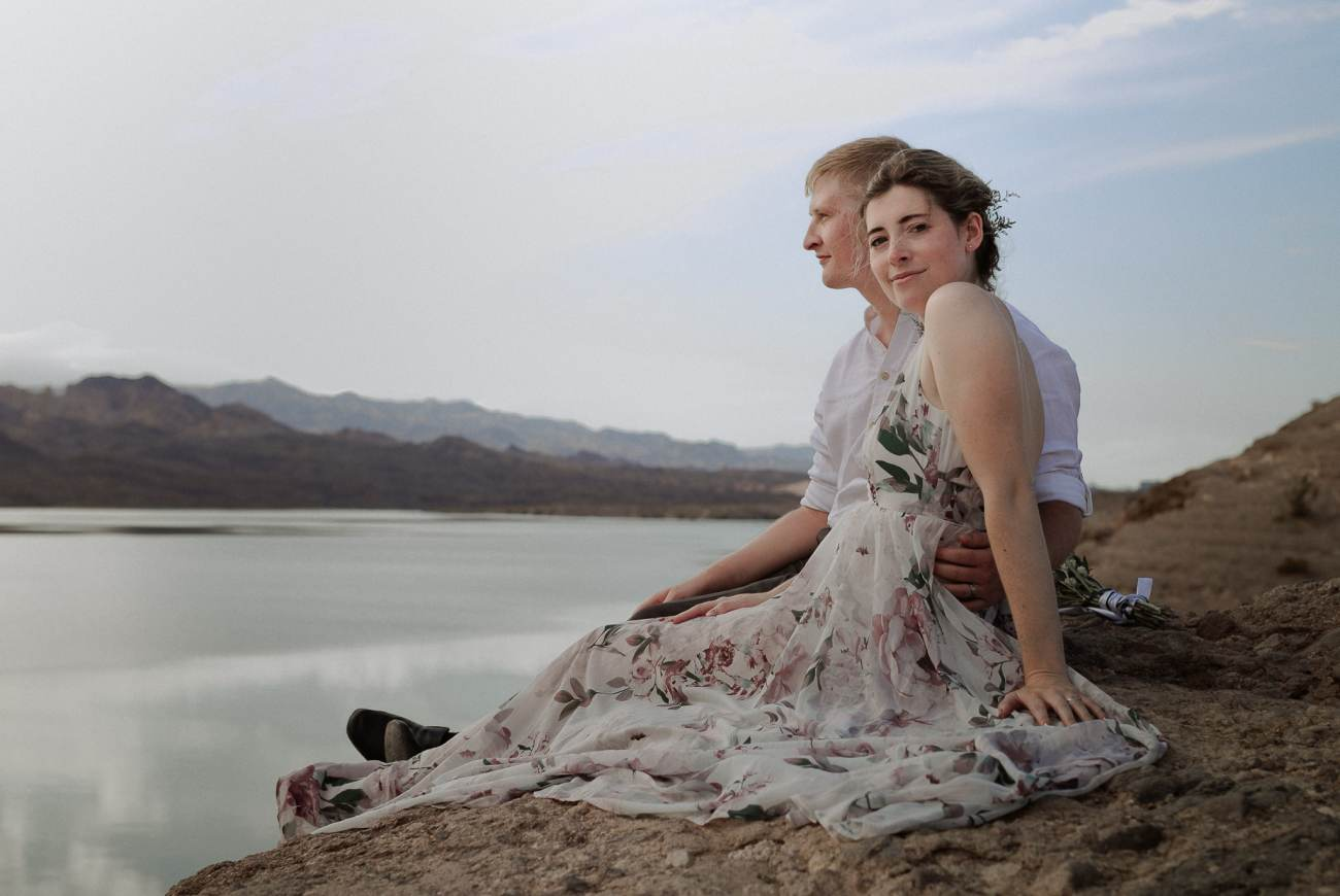 Bride and groom sit on edge of cliff at Nelson's Landing at sunrise