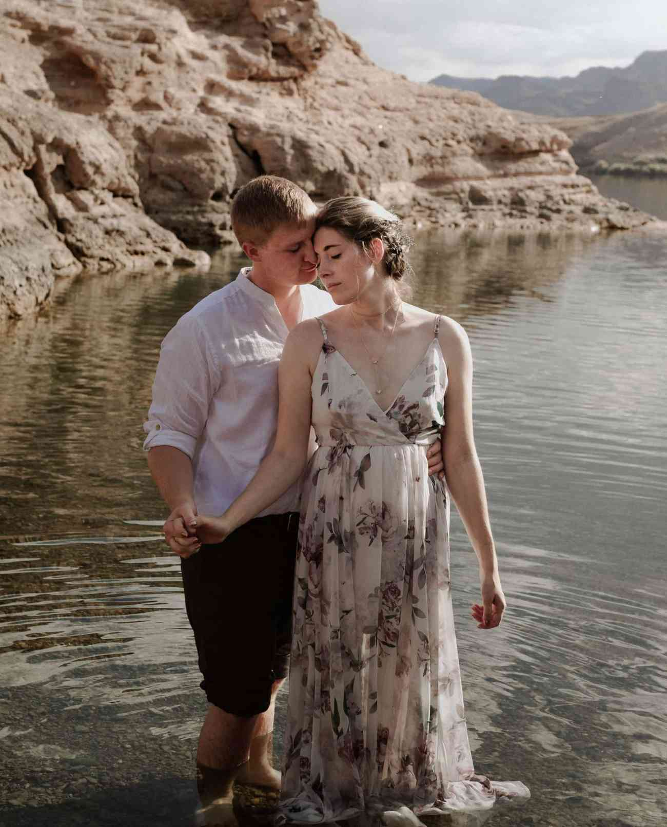 Bride and groom stand in Colorado River at Sunrise caressing each other