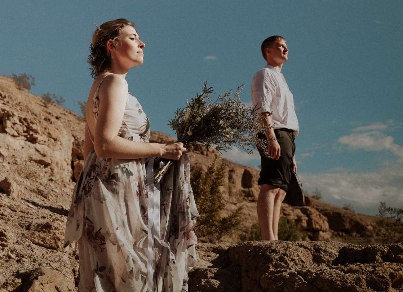 Bride and groom stand on edge of Cliff at Nelson's Landing at Sunrise