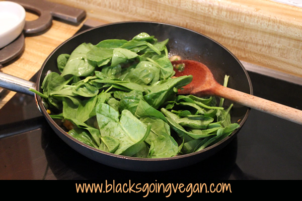 adding baby spinach to sauteed veggies