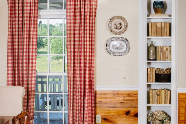 Southern flannel style drapes, decorative plates, and a shelf of books add dimension to this southern decor.