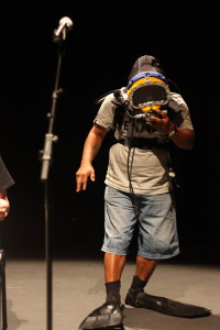a man wearing a diving mask and tank on stage