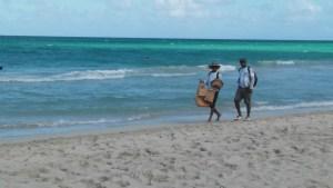 Cuban Merchants walking on the beach