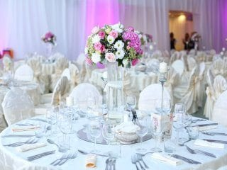 Guest table in white at wedding reception with background uplighting