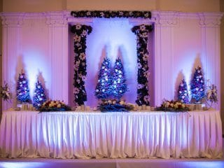 Christmas wedding dessert table with uplighting in ice blue.