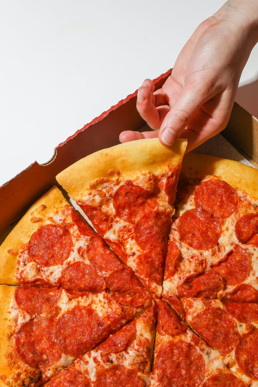 person holding a slice of pizza