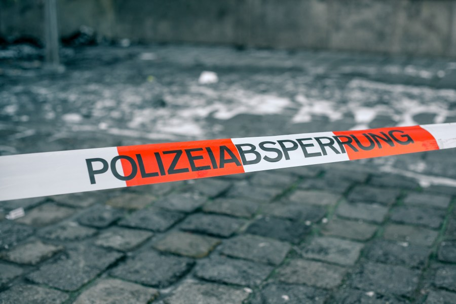 Police tape in Germany at the crime scene with the inscription in German police cordon. Crime Scene.