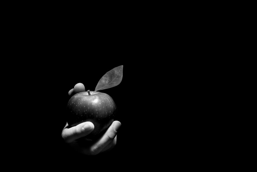 Hand offering an apple.