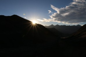Die Sonne blitzt hinter den Bergen hervor.