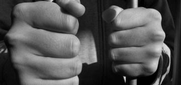 Prison hands bars via Flickr
