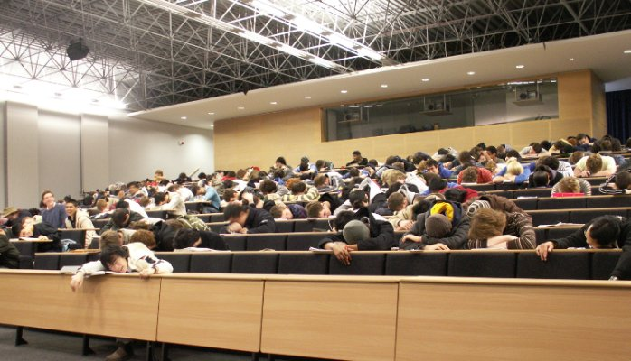 Students asleep in a university lecture hall