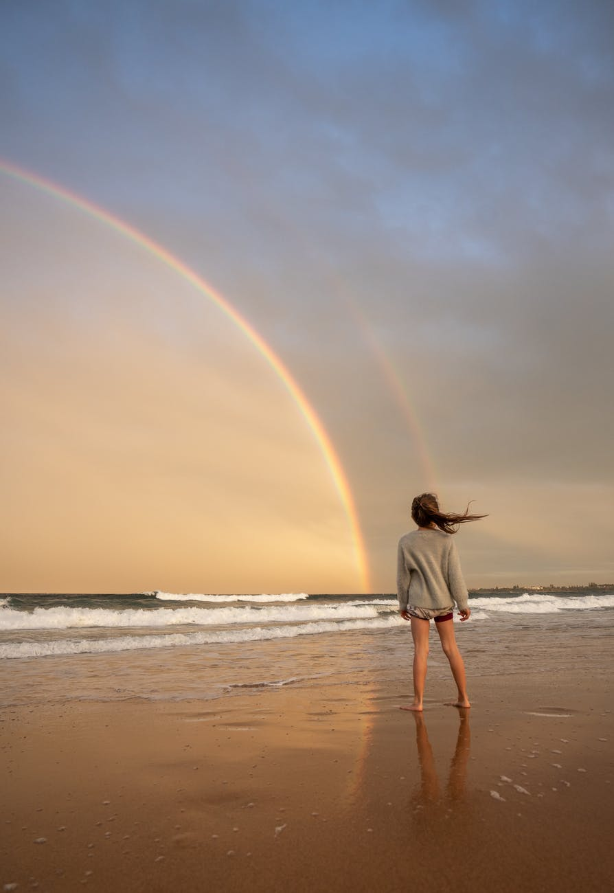 unrecognizable woman standing on shore with rainbow