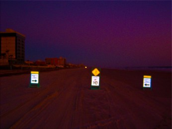 Early morning photograph of traffic signs on the beach, photo edit artwork.