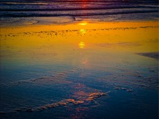 New Art Titled: Sunrise Reflecting on the Beach & Coastline. Unique graphic edit of photograph at sunrise in Daytona Beach of the suns reflection on the water's edge and the waves.
