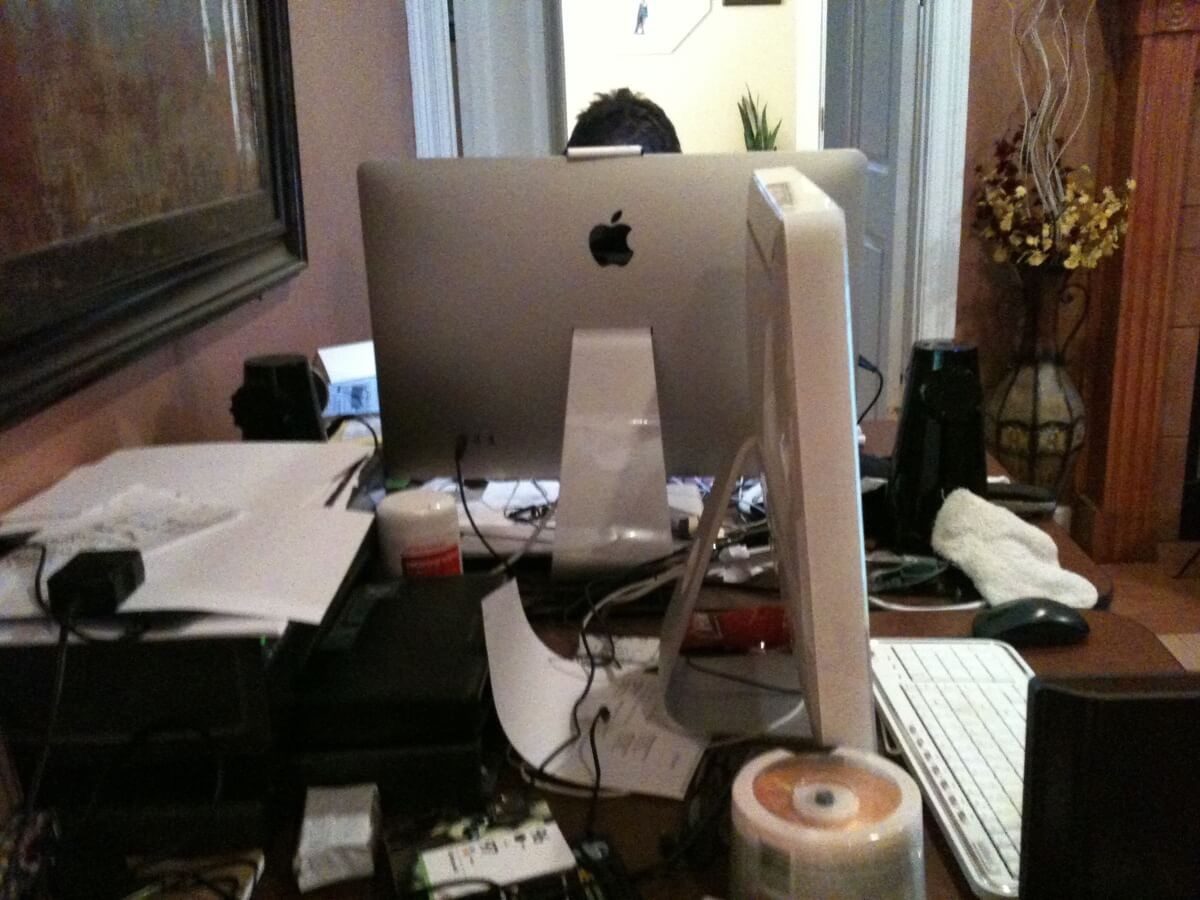 A very messy pair of tables in the living room, each with a Mac. The top of my head is just visible above my Apple Cinema Display.
