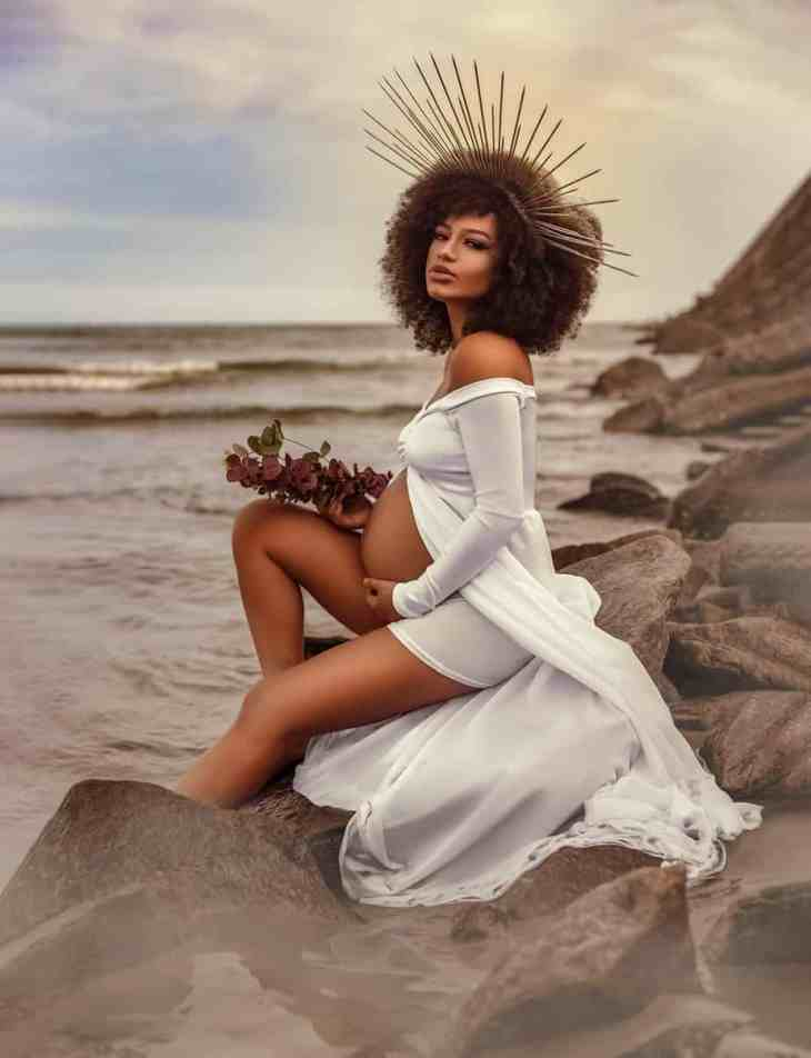 innocent pregnant woman resting on seashore