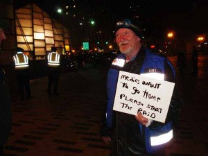 With tense anticipation in the air, Bill the Medic lightened the mood of both police and protestors with a hand-made sign (Blast Staff photo/John Stephen Dwyer)
