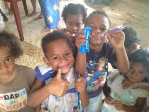 Fijian children in the village of Kanacea gather around to get donated toothbrushes and learn how to clean their teeth.