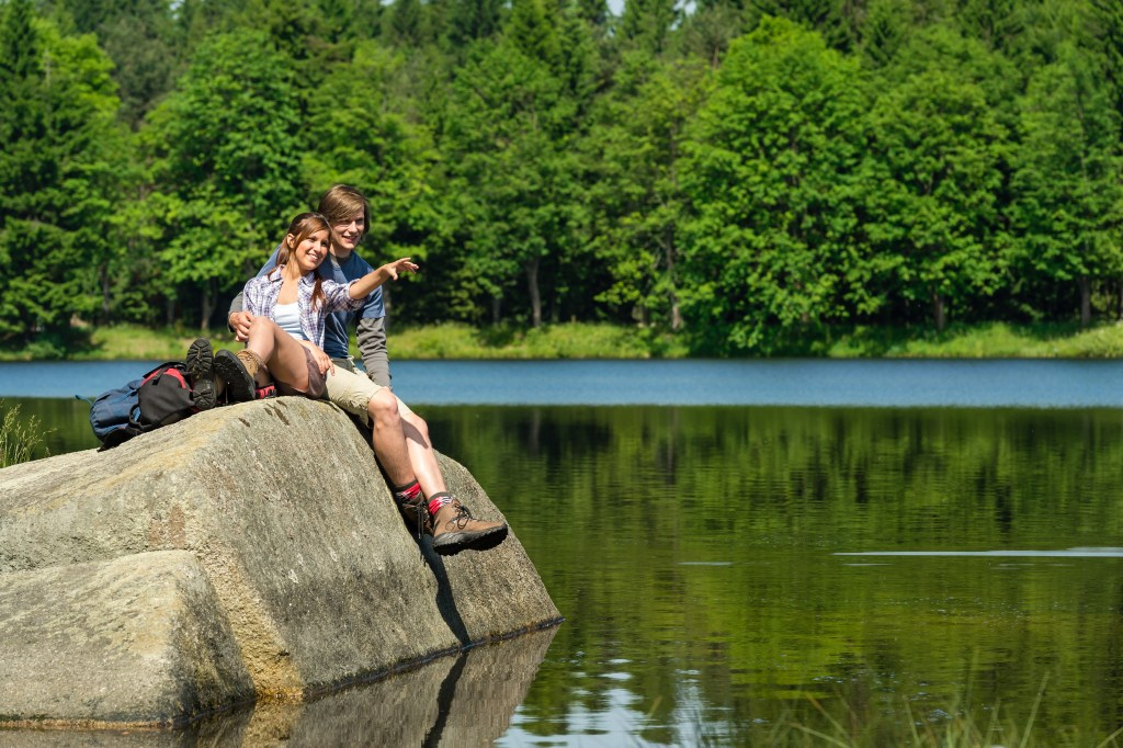 Young hikers couple sitting on rock by the lake