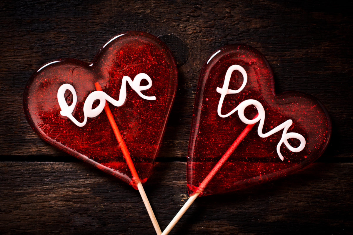Love signs on the heart shape lolly pops on wooden background