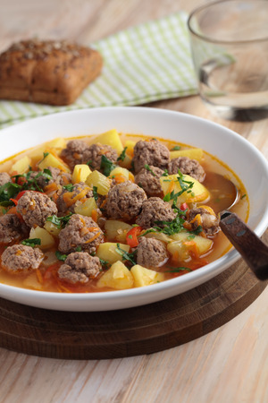 52943589 - meatball soup on a rustic table