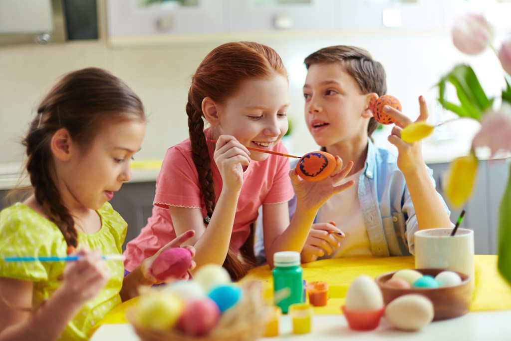 Photo of kids painting Easter eggs at home