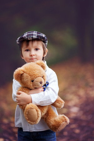 Little boy with suitcase and teddy bear in park