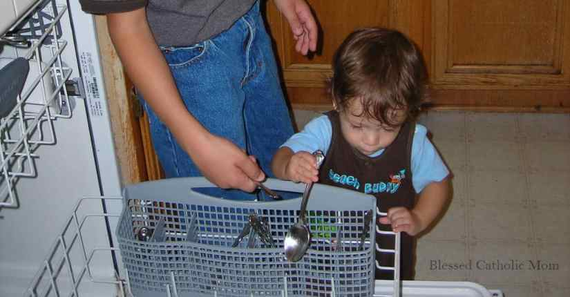 Have kids help with routines to keep the house clean. Image of a toddler boy helping to unload the dishwasher.