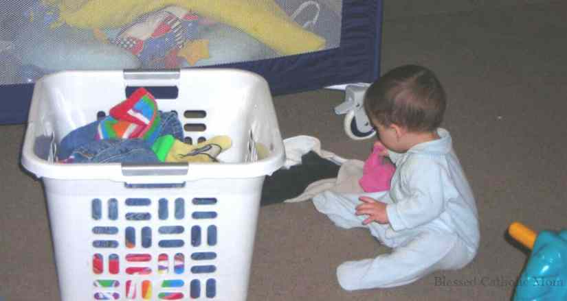 Follow routines every day. Image of a toddler boy helping with laundry.