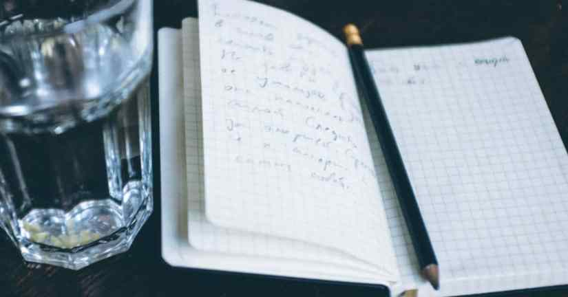 Image of a glass of water by an open book with a pencil on it where someone had written things down on the pages. Image from Barnyard images.