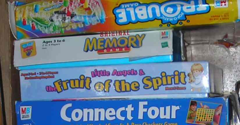Plan a date night with your kids to play and have fun together. Image of a stack of games in a closet.