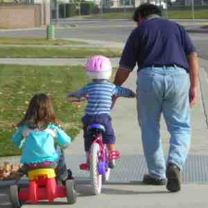 Blessed Catholic Mom: Conquering feelings of overwhelm and nurturing faith to live a more joyful life. Image of a father helping son to ride a bike with daughter on tricycle