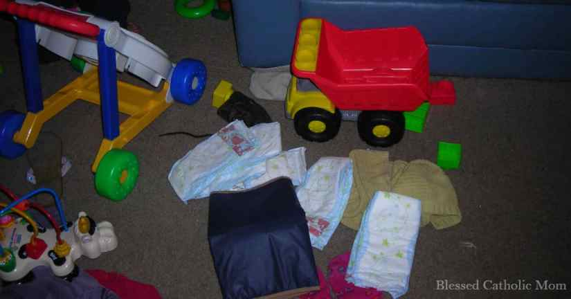 Spend fifteen minutes cleaning up! Image of toys, diapers, and children's clothes on the floor beside a blue couch.